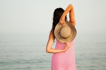 vista-trasera-de-mujer-sosteniendo-su-sombrero_1139-74